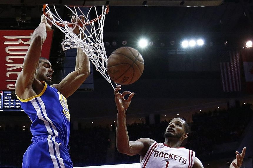 Golden State Warriors power forward James Michael McAdoo dunking over Houston Rockets guard Trevor Ariza in the second half at the Toyota Centre on Friday. McAdoo chipped in with eight points to help his league-leading side (37-6) to a 17th win on th