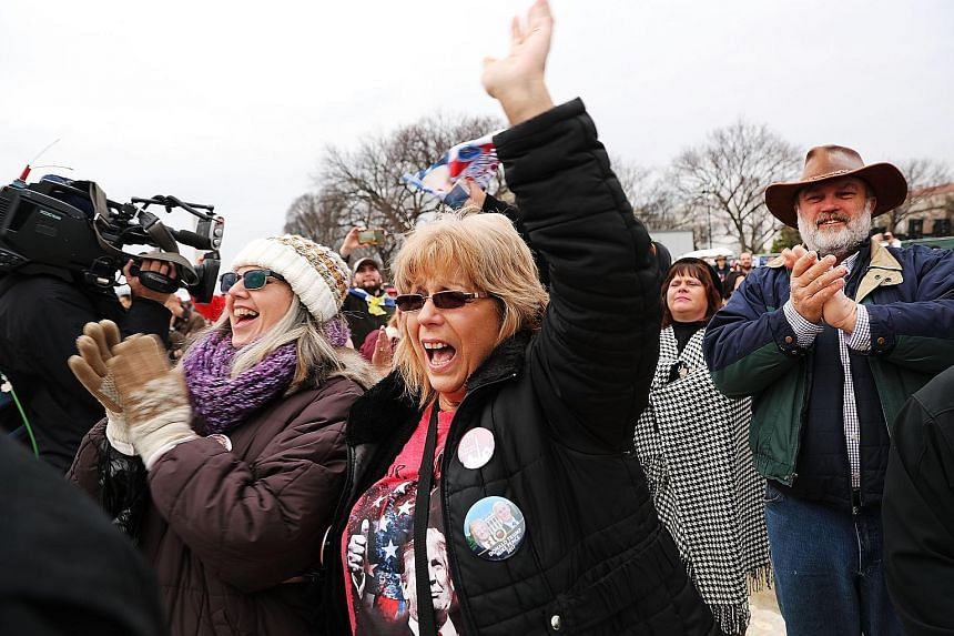 Supporters during Mr Trump's inauguration in Washington, DC, on Friday. Millions of Americans were eager to embrace a Washington outsider willing to say, or tweet, whatever is on his mind.