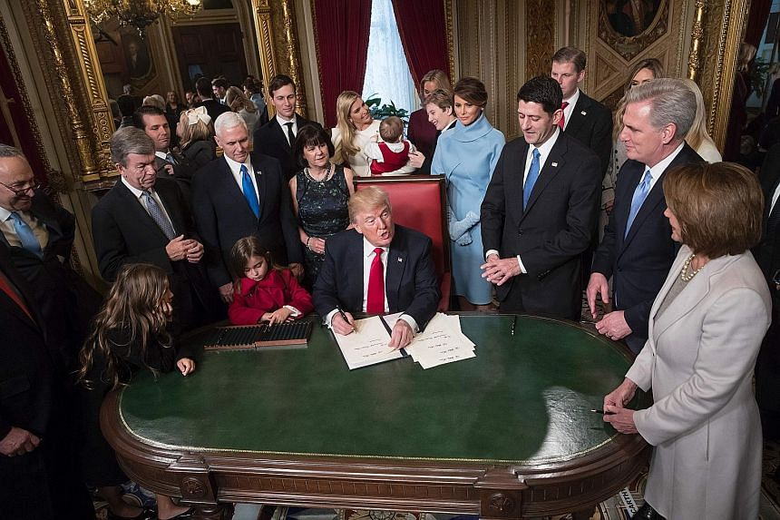 Mr Trump signing two of his Cabinet nominations into law in the presence of the leaders of his administration and Congress as well as his family in the President's Room of the Senate in Washington, DC last Friday. Behind him, his son Barron can be se