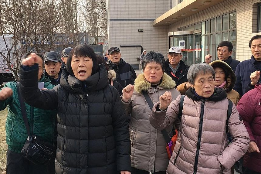 Madam Dai Shuqin (in black) and other relatives of flight MH370 passengers protesting on Wednesday at a monthly meeting with a Malaysia Airlines representative, one day after the official search for the plane was suspended.