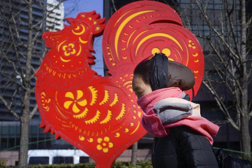 A woman wearing a scarf walks past a lightbox decorated with a rooster sticker at a Central Business District (CBD) in Beijing.