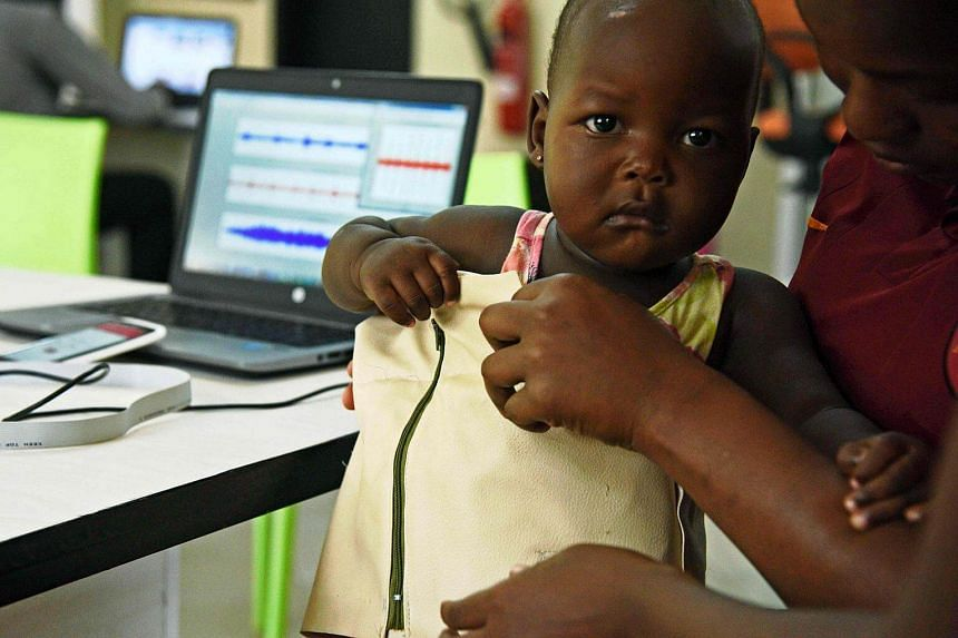 Telecommunications engineer Olivia Koburongo fits a child with the mama-ope kit at the Makerere University of Public Health in Kampala.
