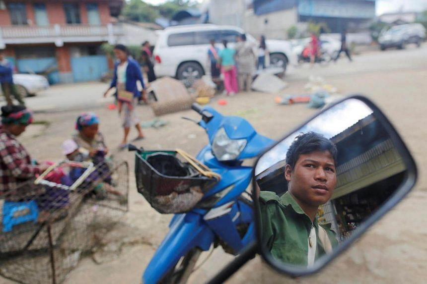A United Wa State Army (UWSA) soldier reflected on mirror as he sits on a motorbike in a market at Mongmao, Wa territory in northeast Myanmar.