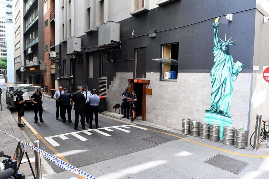 Police officers are seen at a cordoned off area after a man was accidentally shot in Eagle Lane, in Brisbane's central business district, on Jan 23, 2017.