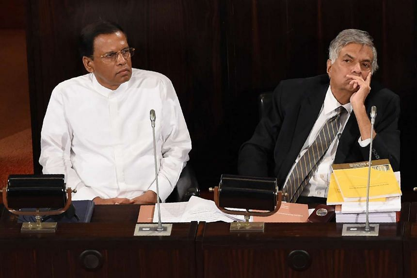 Sri Lankan President Maithripala Sirisena (left) and Prime Minister Ranil Wickremasinghe listen as Sri Lankan Finance Minister Ravi Karunanayake (unseen) presents the 2017 budget to the parliament in Colombo on Nov 10, 2016.