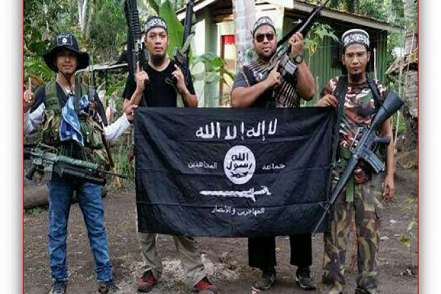 (From left) An Abu Sayyaf fighter with Malaysian militants Mahmud Ahmad, Muhammad Joraimee Awang Raimee and Muamar Gadafi.