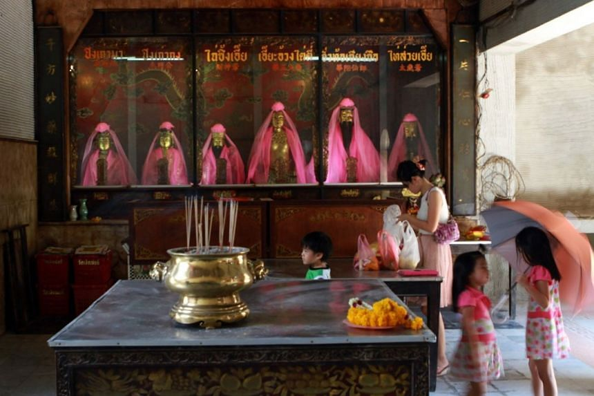 A woman and her children visit Wat Mangkon Kamalawat during the Chinese New Year period.