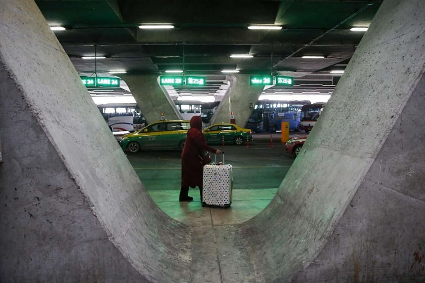 A traveller pushes the baggage as taxis wait for passengers outside of the Suvarnabhumi Airport in Bangkok, Thailand.