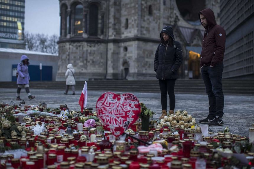 People look at flowers and candles mourners placed on the Breitscheid square in Berlin, Germany on Jan 18, 2017. Twelve people died when a man deliberately steered a truck into a Christmas market on Dec 19, 2016.