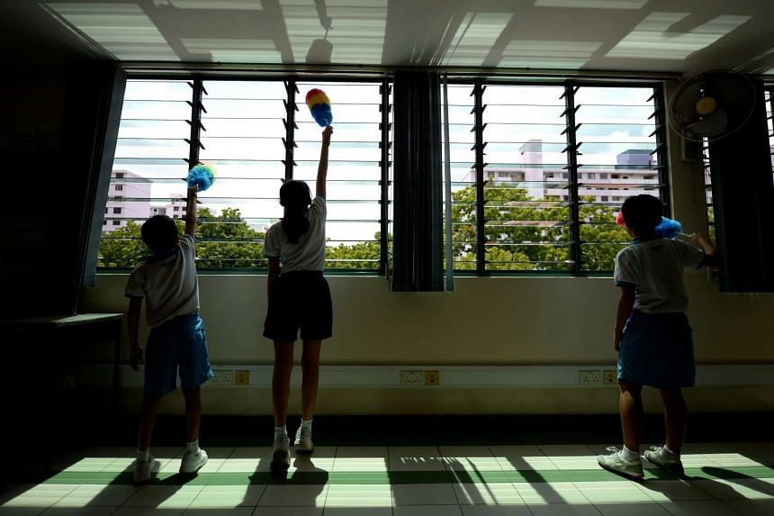 Primary 5 pupils at Xinmin Primary School cleaning their classroom. At the end of each school day, a chime is played five minutes before dismissal, signalling the start of the daily cleaning activities.