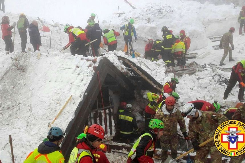 Rescue workers search around the Hotel Rigopiano in Farindola, central Italy, hit by an avalanche, in this undated picture released on Jan 22, 2017 provided by Alpine and Speleological Rescue Team.