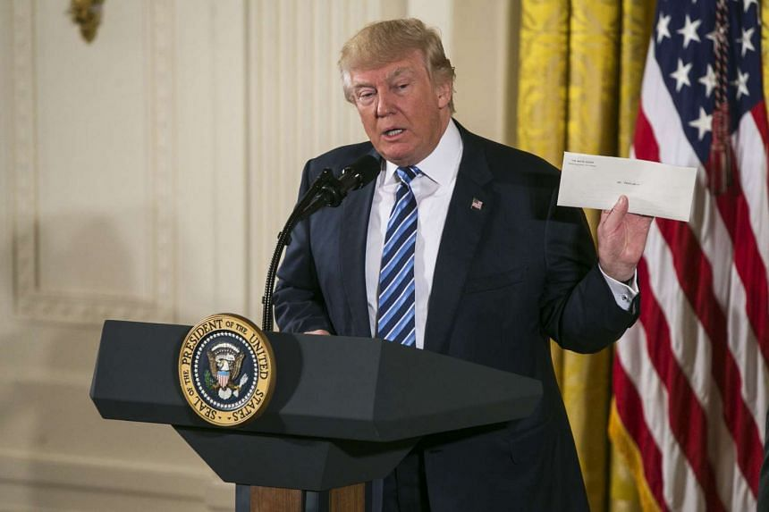 President Donald Trump holds up a letter from former President Barack Obama at the White House senior staff swearing-in ceremony in Washington on Jan 22, 2017.