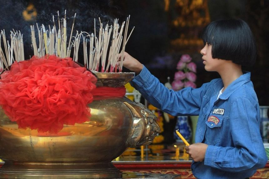 A young girl pays homage to the goddess Kuan Yin at the Thian Fa Foundation in Yaowarat, located in Bangkok's Chinatown.