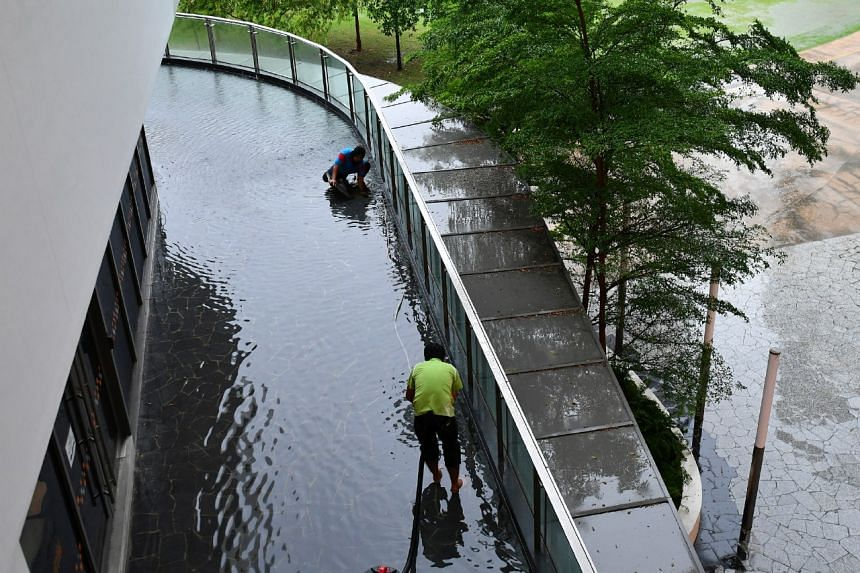 Workers trying to clear the flooded walkway at NUS University Town on Jan 23, 2017.
