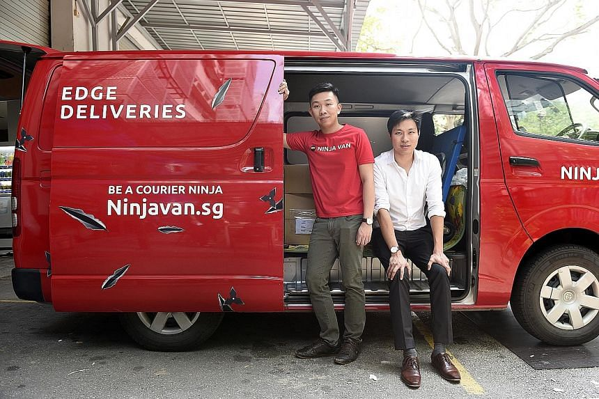 Ninja Van's Mr Pang (standing), seen here with Sunseap's Mr Tan, says his company has saved on electricity costs since switching to Sunseap's GoEco plan for one of its two facilities last month.