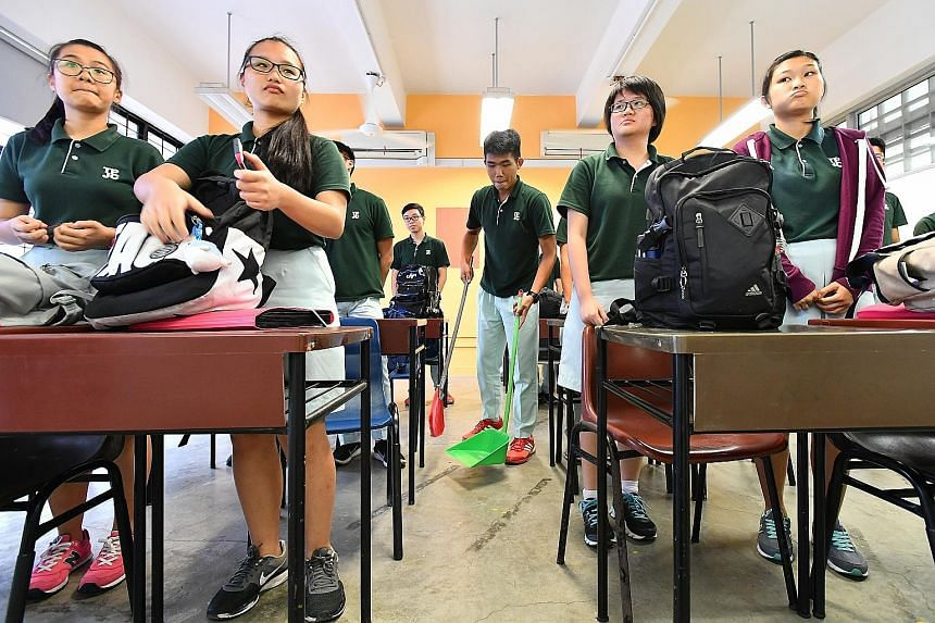 TPJC student Jaydon Chong Wei Ler (centre) sweeping the floor after a lesson. First-year students at the junior college assist the cleaners, even with cleaning the toilets, as part of Project Kirei, a student-driven initiative.