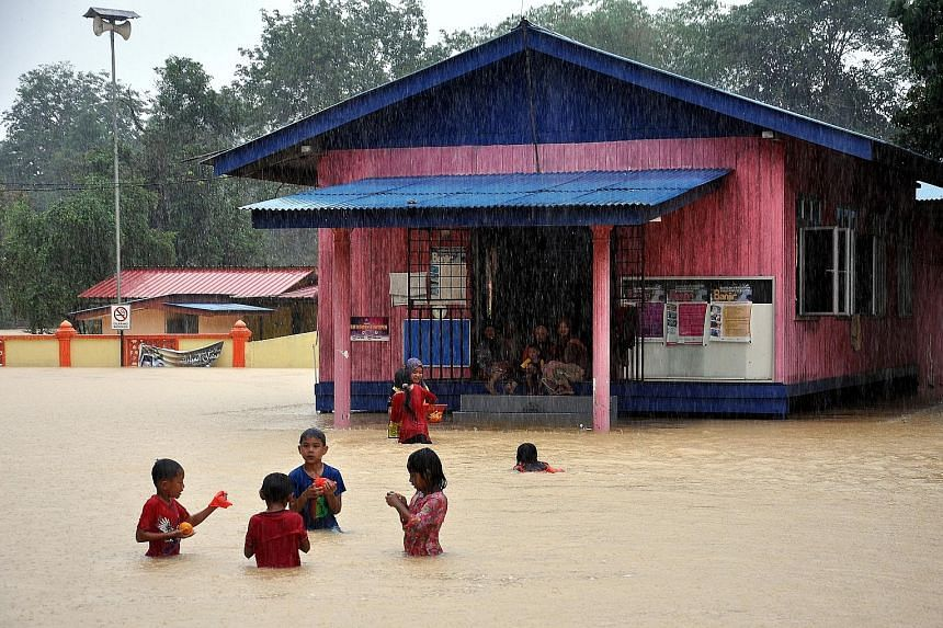 Children, undaunted by floodwater, playing in front of the Kampung Tasik flood relief centre in Setiu, Terengganu, on Saturday. MetMalaysia issued a heavy rain warning for the state and Pahang yesterday, and said it expected moderate rain to continue