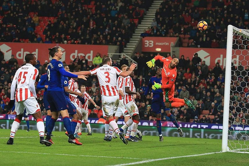 Stoke goalkeeper Lee Grant can only look on helplessly as Wayne Rooney's free kick sails past him into the top corner. The Manchester United forward's goal was his 250th for the club, taking him past the legendary Bobby Charlton as the club's record