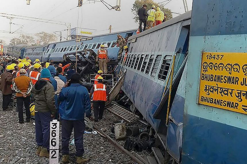 Rescue workers looking for survivors yesterday at the site of the train crash in India's southern Andhra Pradesh state. The train was travelling from the city of Jagdalpur to Bhubaneswar on Saturday night when it derailed, and officials are investiga
