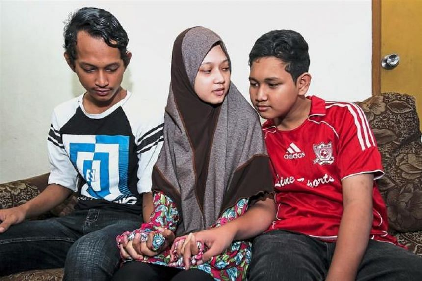 The three siblings (from left) Muhammad Ridzuan, Nur Hidayah and Muhammad Firdaus. Firdaus, 14, was also stricken with dengue.