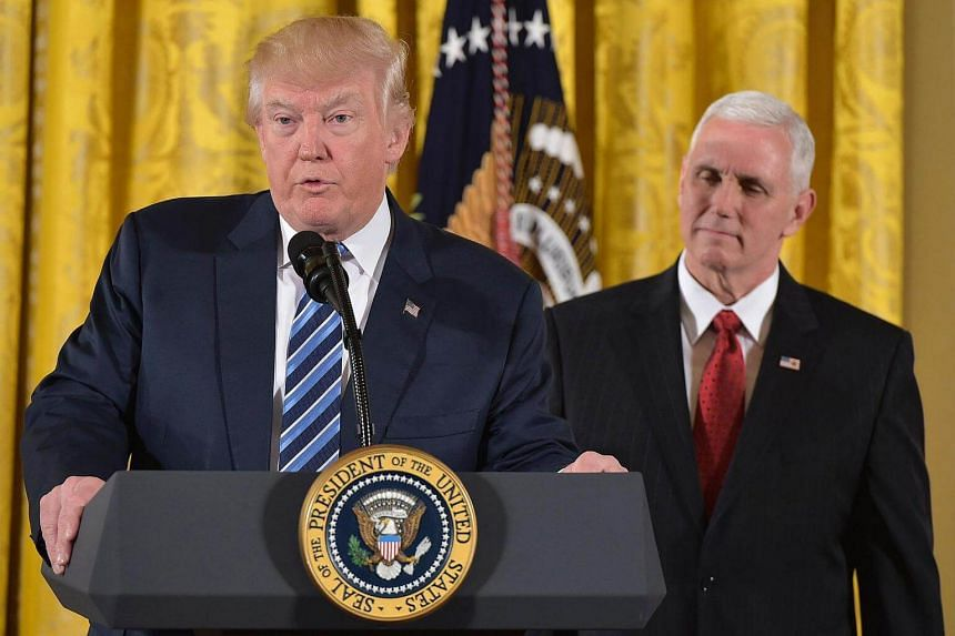 US President Donald Trump speaks, as Vice President Mike Pence watches, before the swearing in of the White House senior staff at the White House on Jan 22, 2017.