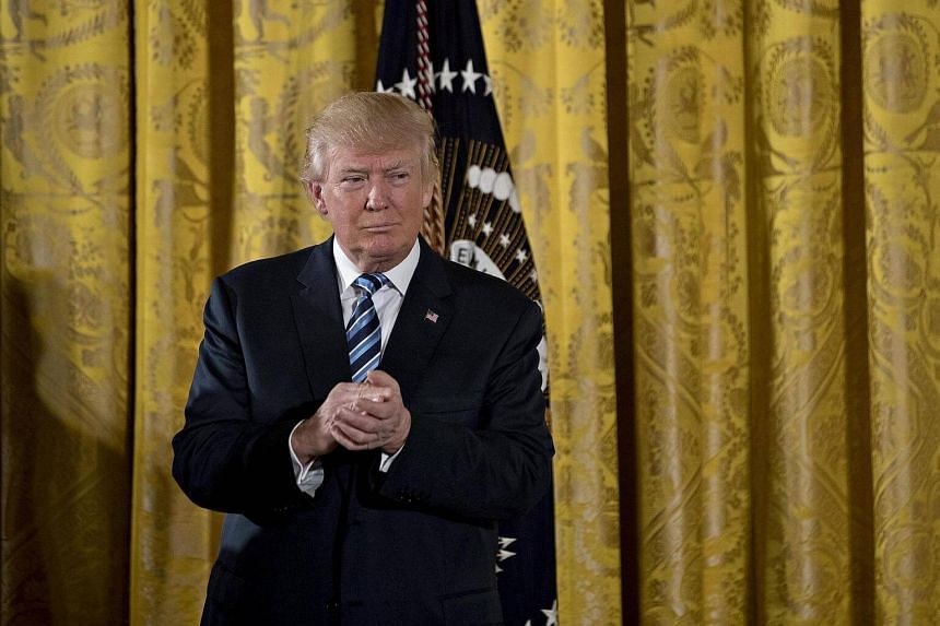 US President Donald Trump listens during a swearing in ceremony of White House senior staff in the East Room of the White House in Washington, DC on Jan 22, 2017.