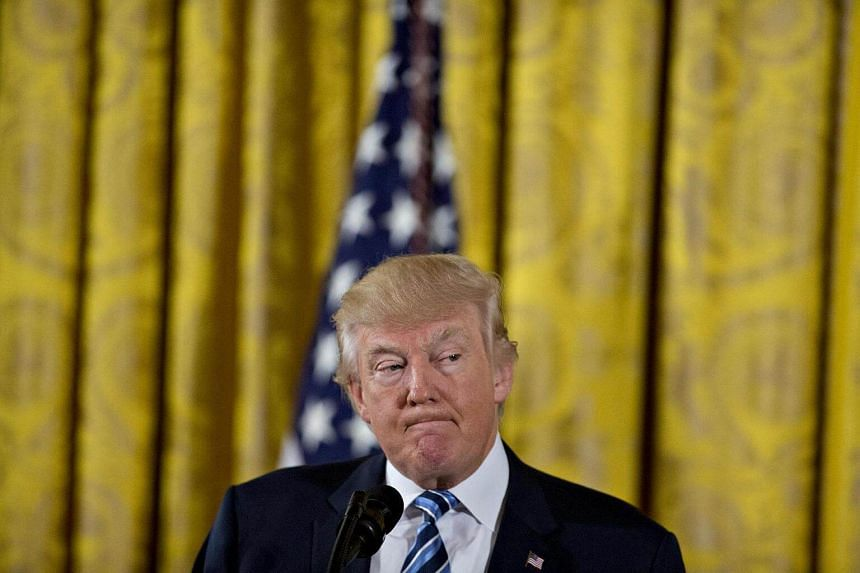 US President Donald Trump pauses while speaking during a swearing in ceremony of White House senior staff in the East Room of the White House in Washington, DC, on Jan 22, 2017.