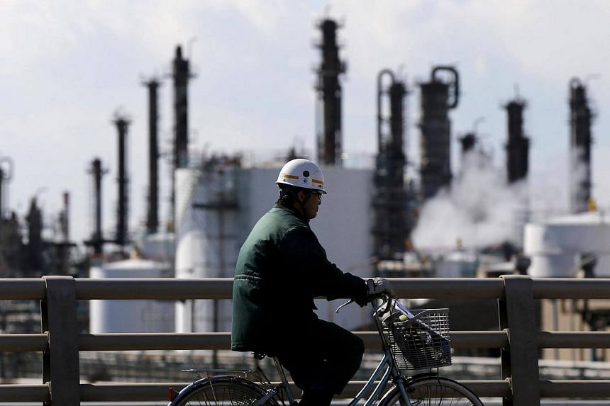A worker cycles near a factory at the Keihin industrial zone in Kawasaki, Japan.
