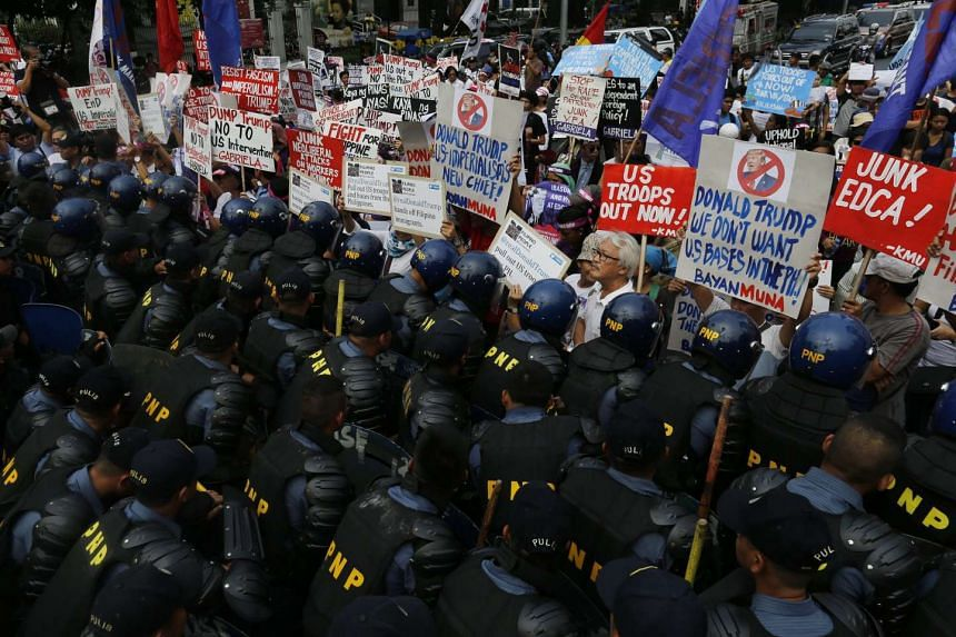 Protesting Filipinos and Fil-Americans are blocked by anti-riot policemen during a protest rally in front of the US embassy in Manila, Philippines, on Jan 20, 2017.