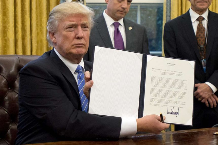 US President Donald Trump showing the Executive Order withdrawing the US from the Trans-Pacific Partnership (TPP) after signing it in the Oval Office of the White House in Washington, DC, on Jan 23, 2017.