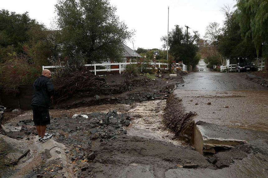 A man watching floodwaters flowing over a street during a rain storm in Santa Clarita, California.
