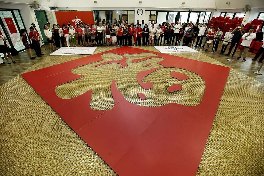"More than 1,500 participants baked and toiled over two weekends to make their mark in the Singapore Book Of Records with ""The Largest Chinese Character Made With Pineapple Tarts"". The tarts - numbering more than 25,000 - were assembled in an 88 sq m"