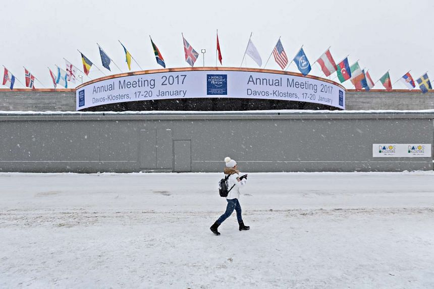 A woman passes security walls shielding the entrance to the venue for the World Economic Forum (WEF), in Davos, Switzerland, on  Jan. 13, 2017.