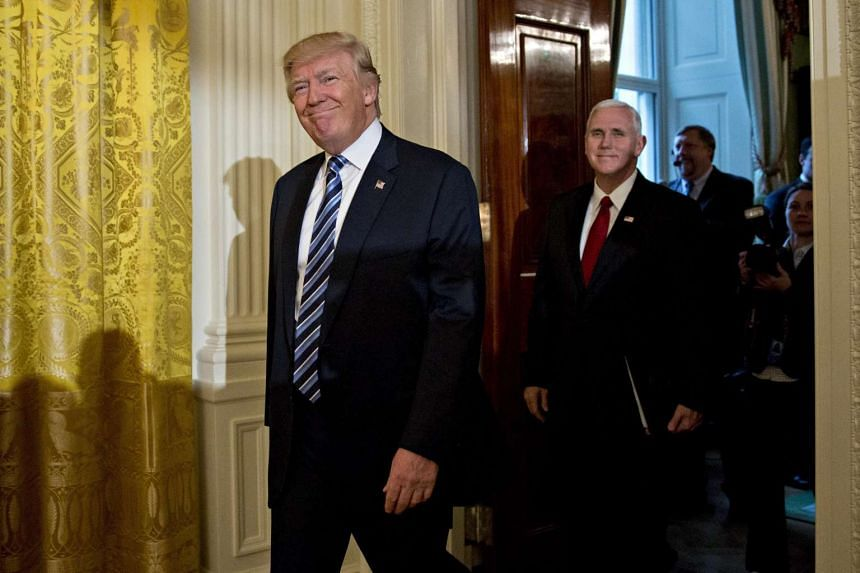 US President Donald Trump, left, and US Vice President Mike Pence arrive to a swearing in ceremony of White House senior staff in the East Room of the White House in Washington, DC, USA, on Jan 22, 2017.