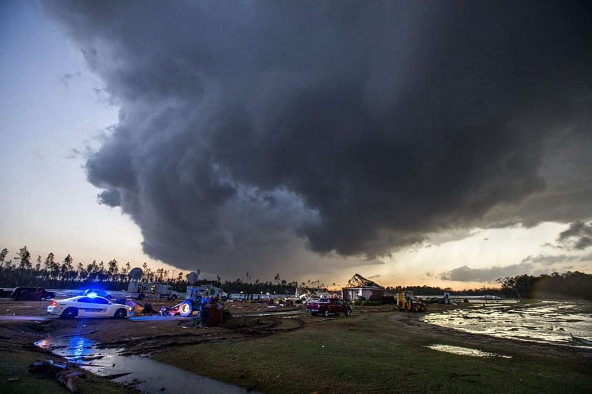Storm clouds approach emergency crews at the scene of a house cut in half by a tornado near where seven people were killed outside Adel, Georgia USA on Jan 22, 2017.