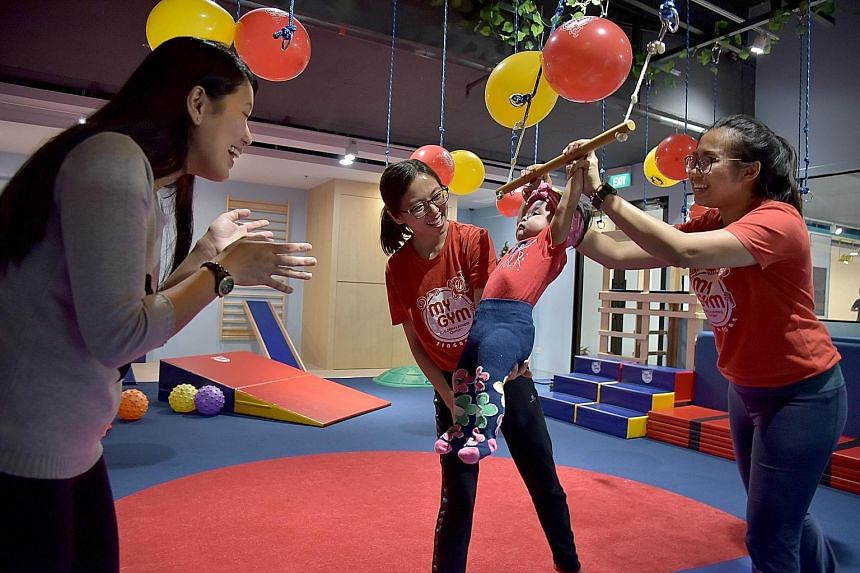 Madam Joanne Oglimen (left) watching her seven-month-old daughter Nathalia Yambao playing on a swing, supervised by gym coaches at the Bove megastore in Suntec City yesterday. Besides selling maternity wear and baby products, the store has play areas