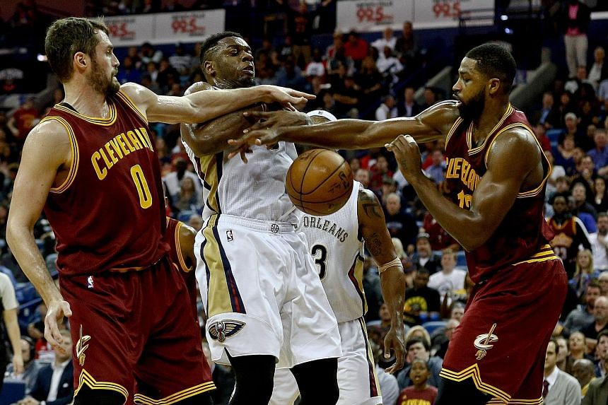New Orleans Pelicans forward Terrence Jones (centre) is thwarted by a joint effort from Cleveland Cavaliers duo Kevin Love (left) and Tristan Thompson (13) on Monday. Jones matched his career-best performance with 36 points in the 124-122 victory ove