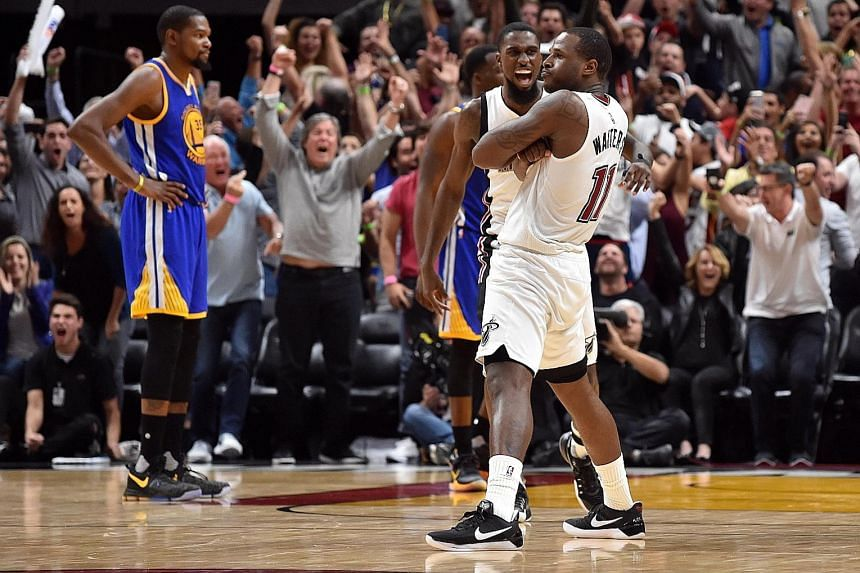 Miami Heat guard Dion Waiters (No. 11) celebrating hitting the game-winning basket against the Golden State Warriors. The Heat upset the league-leading Warriors 105-102.