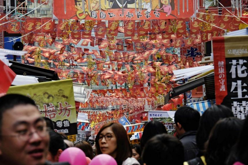 Flags with rooster patterns hang over the crowd as local residents shop in a traditional market in Taipei.