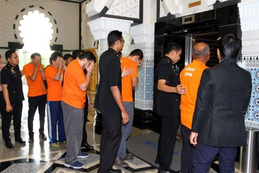 The Felda officials, who have been remanded as part of investigations into alleged corruption and power abuse, being led into the magistrate's court in Putrajaya.