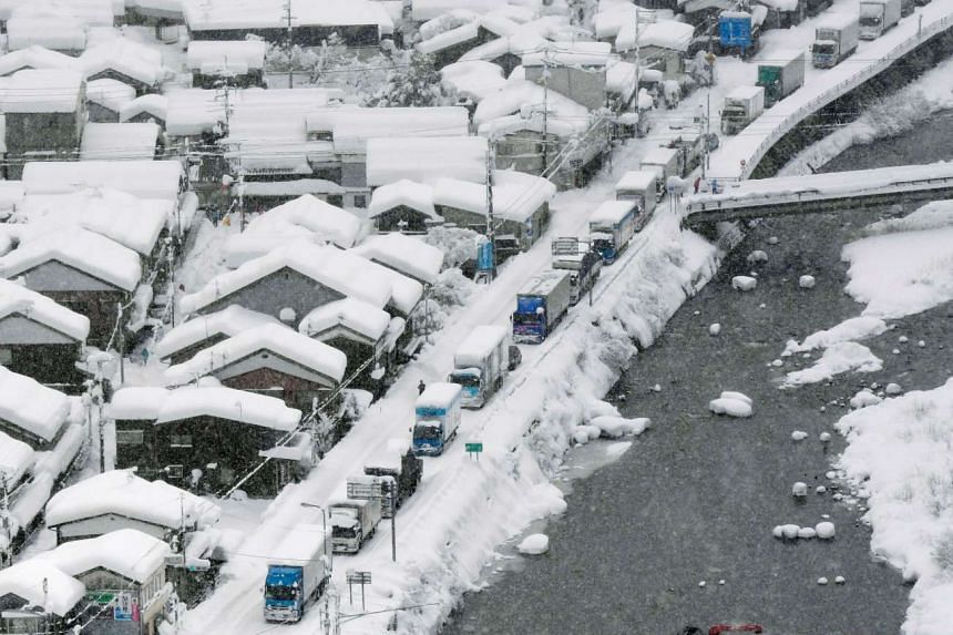 Vehicles stuck after heavy snow blanketed the town of Chizu in Tottori prefecture yesterday. Japanese troops were mobilised to help dig out the vehicles.