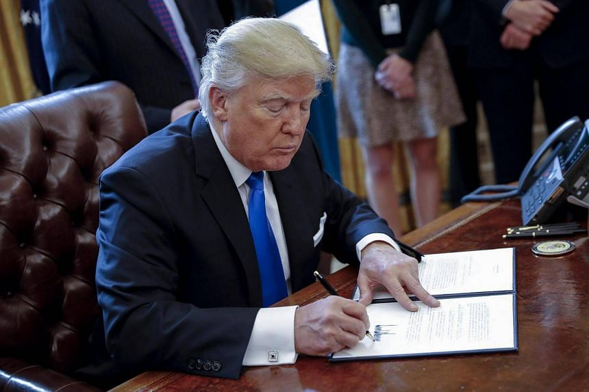 US President Donald Trump signing one of five executive orders related to the oil pipeline industry in the oval office of the White House in Washington, DC, on Jan 24, 2017.