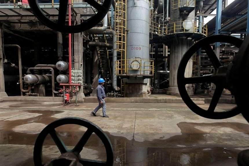 A worker walks past oil pipes at a refinery in Wuhan, Hubei province on Mar 23, 2012.