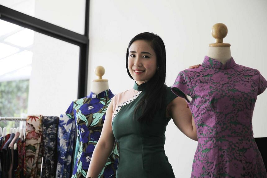 Lark and Peony founder Junie at home posing with her cheongsam designs.