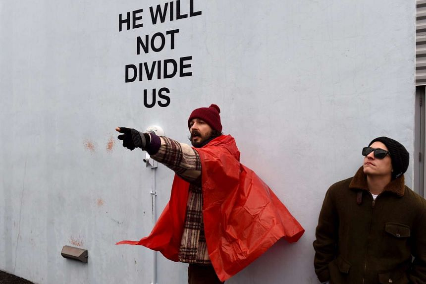 "US actor Shia LaBeouf (left) during his ""He Will Not Divide Us"" livestream outside the Museum of the Moving Image in Astoria, in the Queens borough of New York on Jan 24, 2017 as a protest against President Donald Trump."