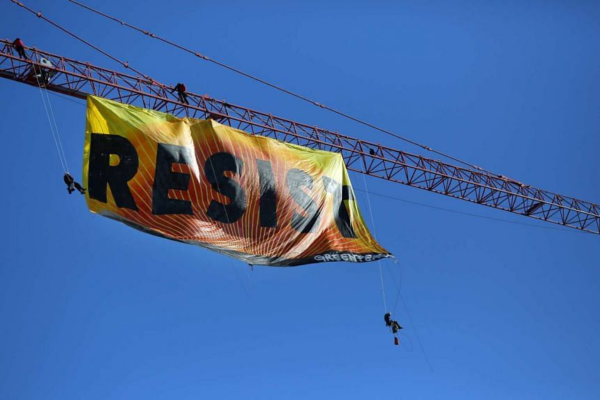 Greenpeace activists hold an anti-Trump protest as they display a banner reading 'Resist' from a construction crane near the White House in downtown Washington, US on Jan 25, 2017.
