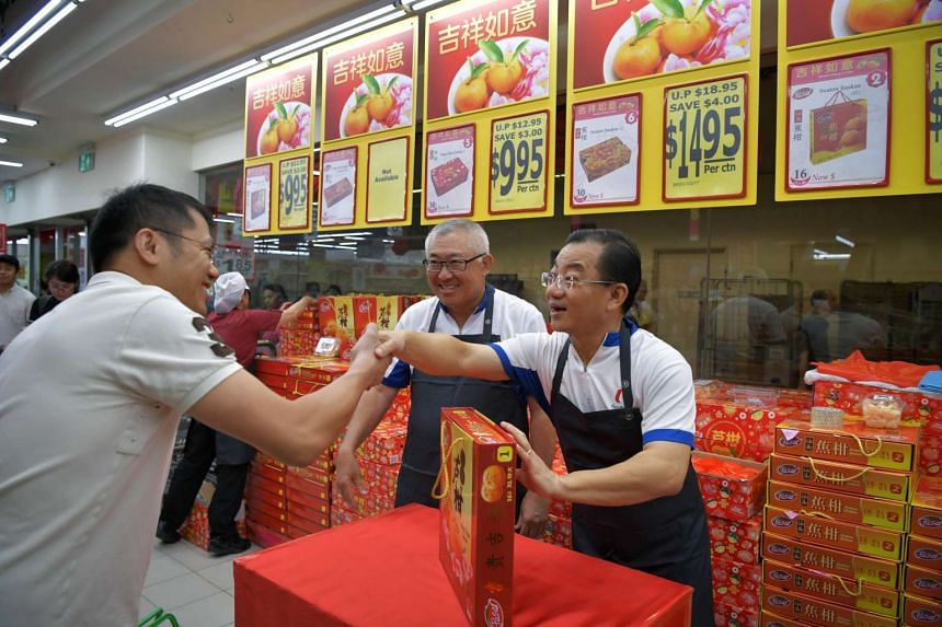 Mr Seah Kian Peng (right) and Mr Bobby Chin (centre) sorting and distributing mandarin oranges as they participate in the One FairPrice Family Programme.