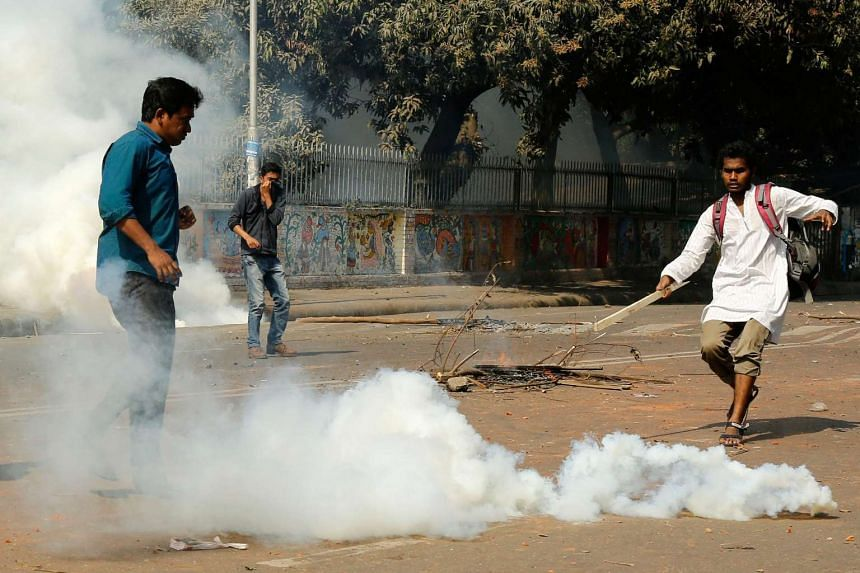 A protester attempts to kick a tear gas canister fired by policemen during a protest against the Rampal coal-fired power plant, near Shahbag, Dhaka, Bangladesh on Jan 26, 2017.