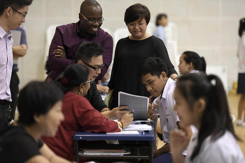 A student from Serangoon Garden Secondary School, receives his O Level results from his teachers.