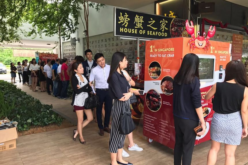People queue to buy chilli crab from House of Seafood's Ready-to-Eat-Crab vending machine.